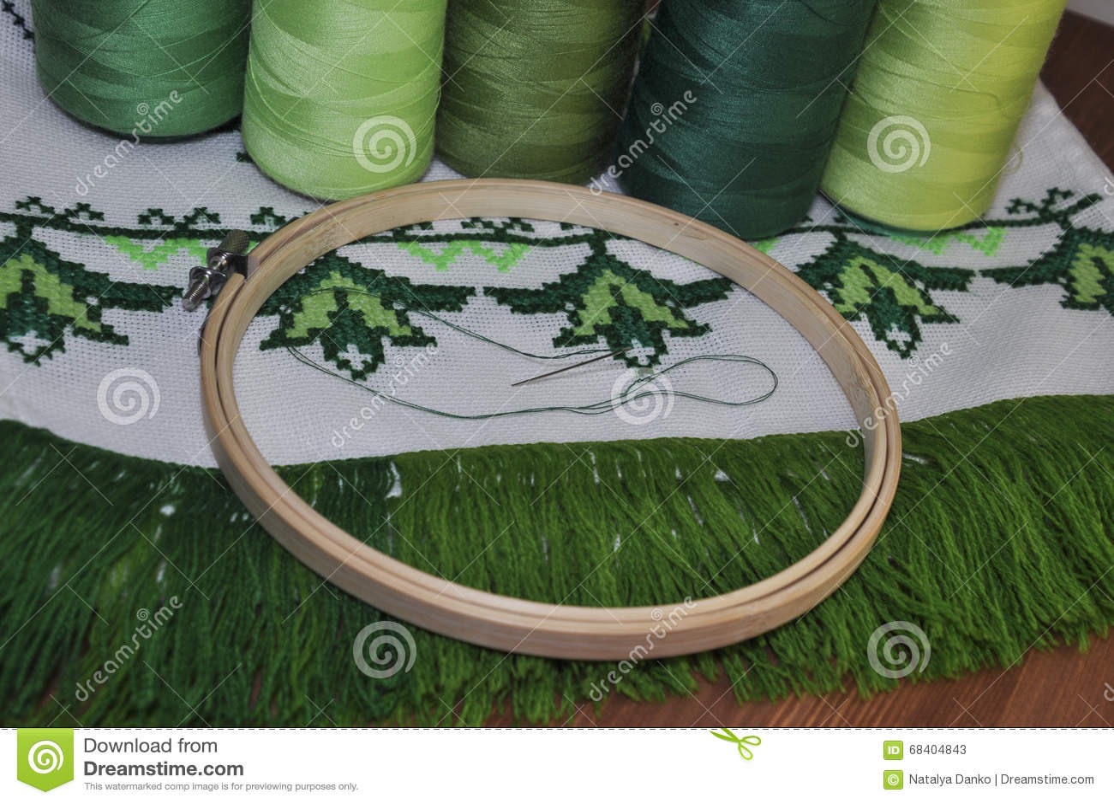 Cousez au point de croix la serviette en bois de cadre de broderie dans le threa vert clair