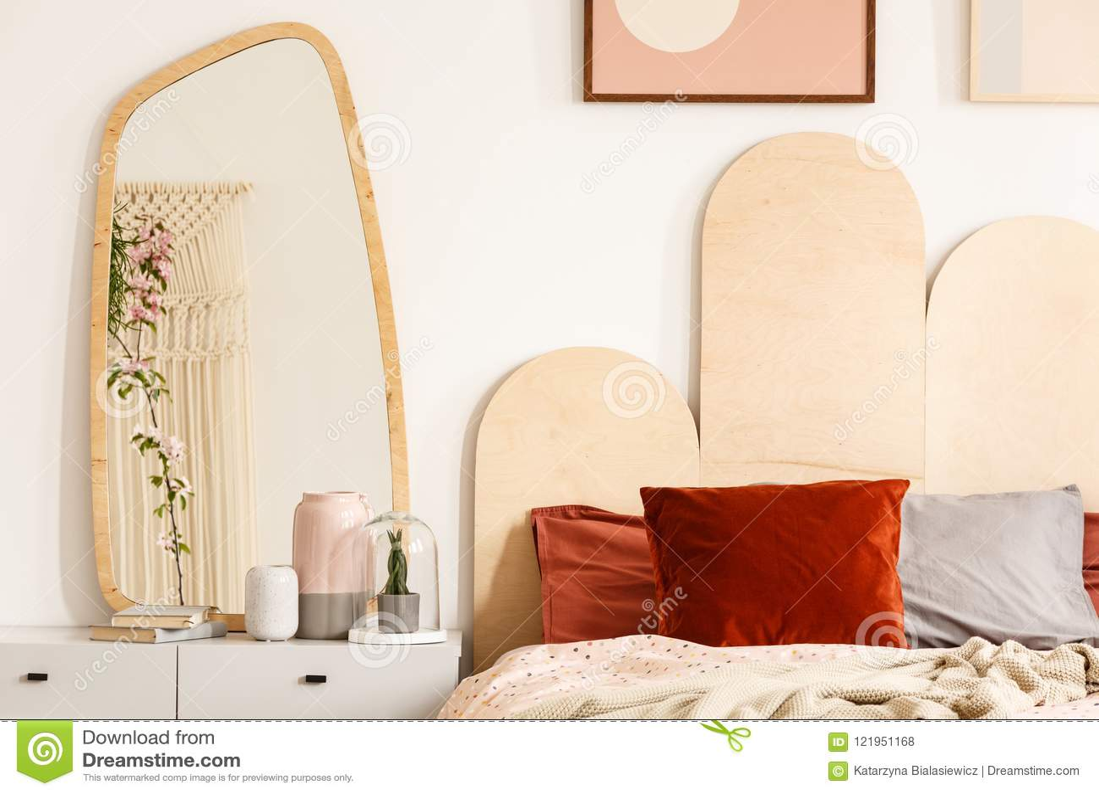 Coussins rouges sur le lit avec la tête de lit à côté de la coiffeuse avec m