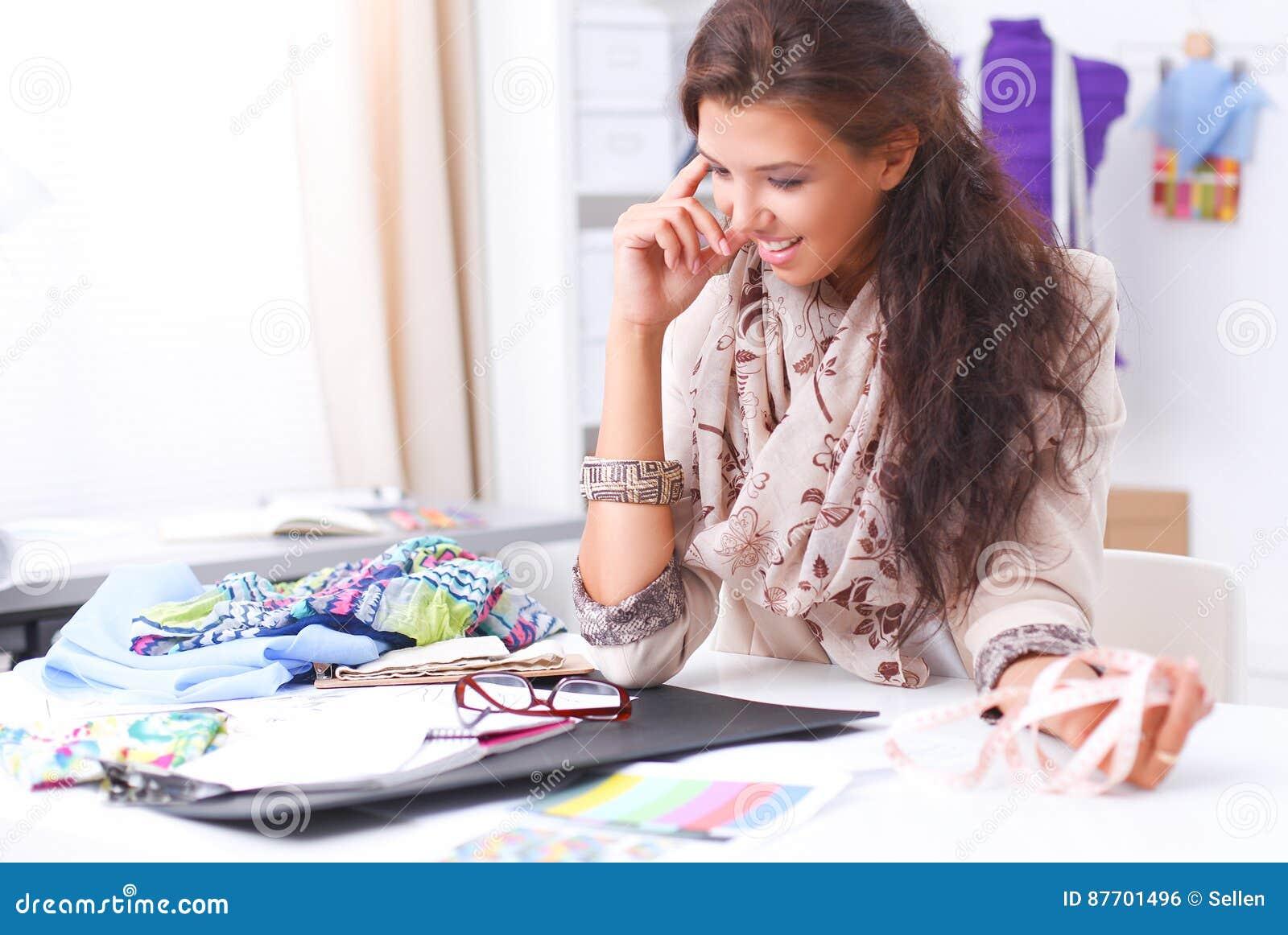 Couturier féminin de sourire s asseyant au bureau