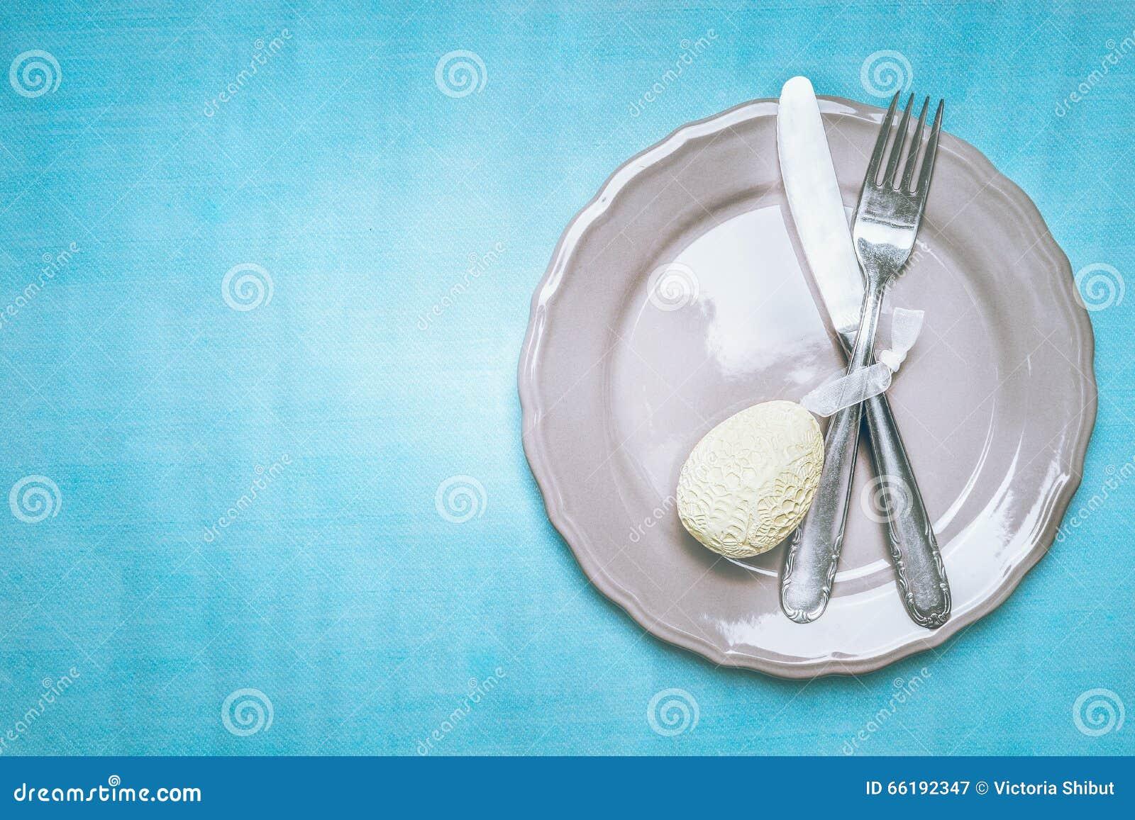 couvert de table de p ques avec le plat les couverts et l 39 oeuf de p ques sur le fond bleu vue. Black Bedroom Furniture Sets. Home Design Ideas