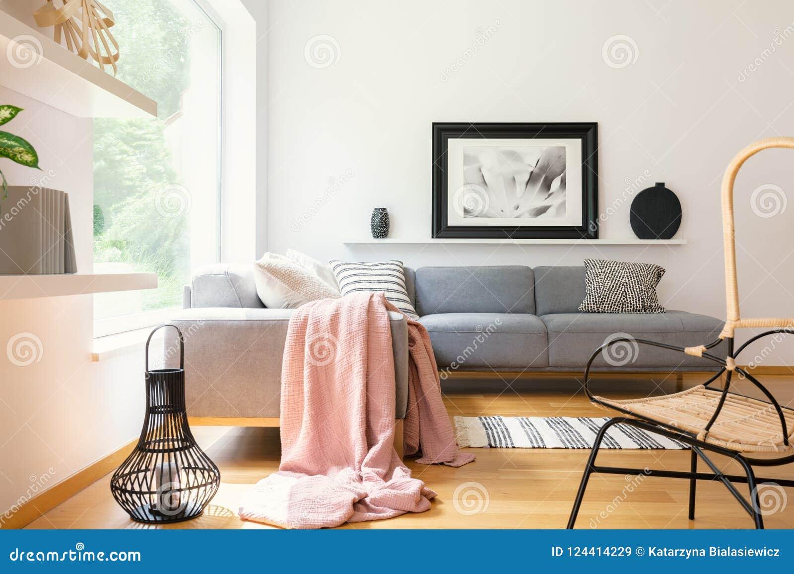 Couverture de rose en pastel jetée sur le divan faisant le coin se tenant dans l intérieur blanc de salon avec l affiche simple,