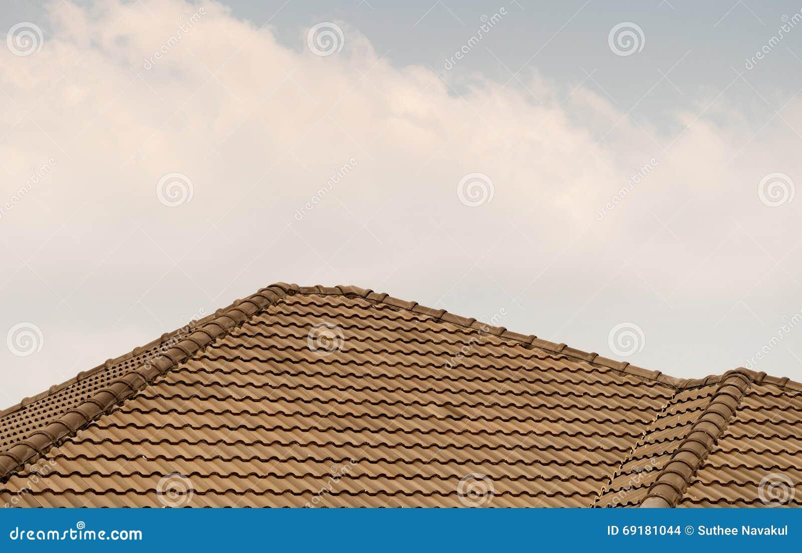 Couvrez la maison de toit carrelé sur le ciel bleu