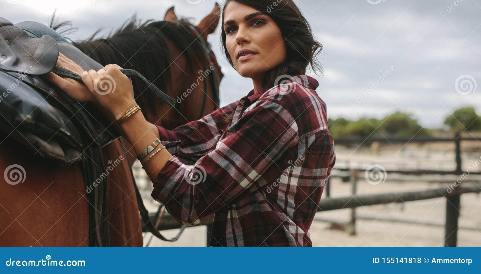 Cow-girl sellant un cheval brun