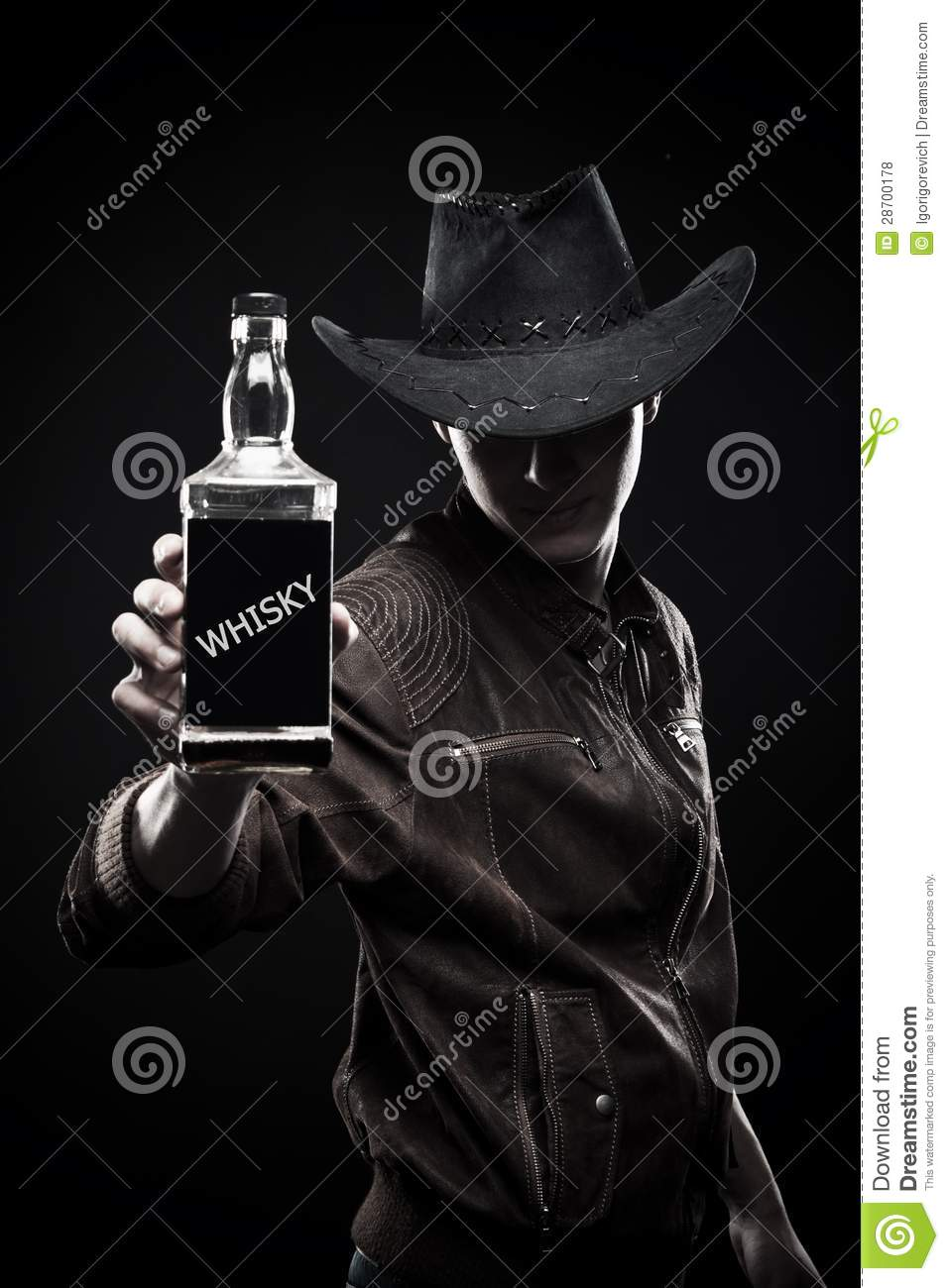 4ce89fe4c64 Macho in cowboy hat with bottle of whisky posing over dark background