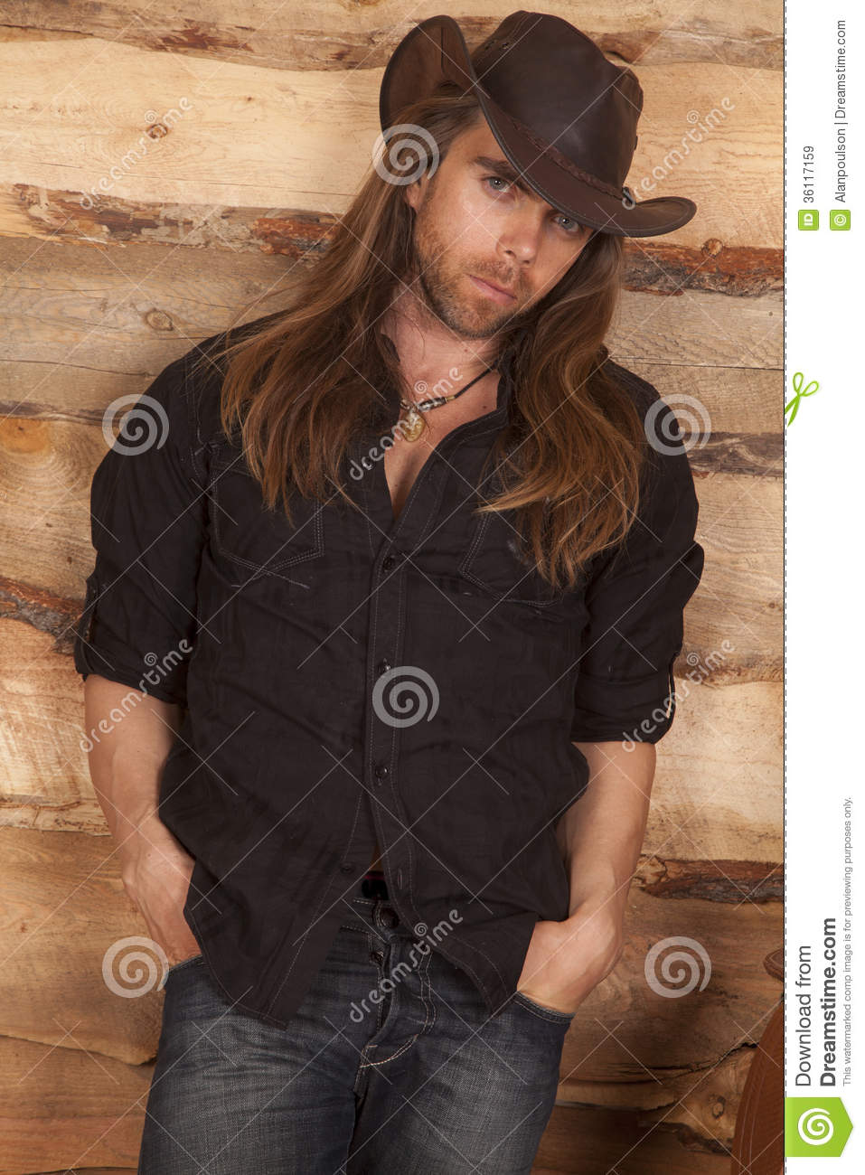 b6b21603dc1d4 A cowboy leaning up against a wood wall with a serious expression on his  face.