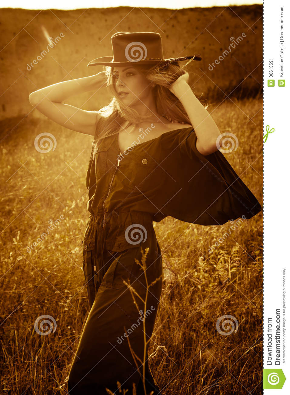 Young woman in cowboy style clothes outdoor at sunset