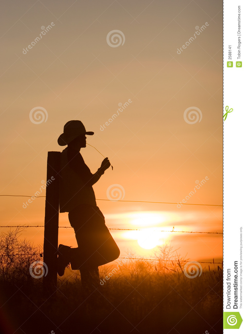 Silhouette of cowboy leaning against fence post watching the sun set.