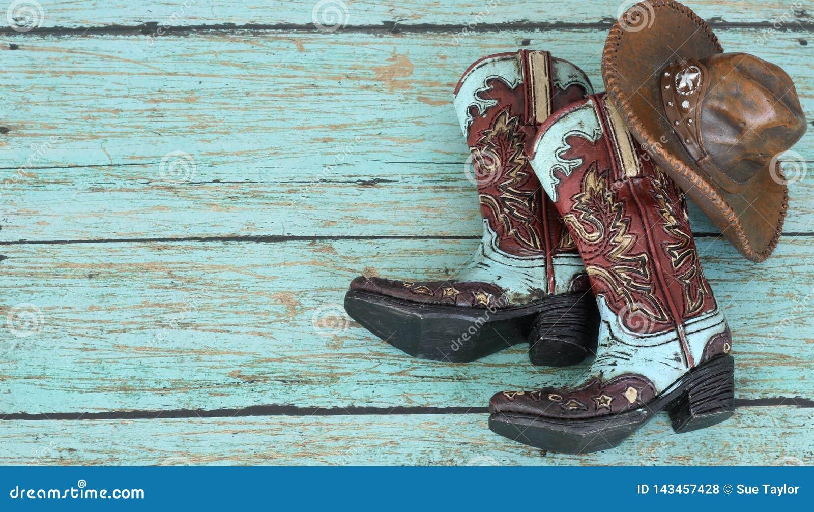 Cowboystiefel und Hut auf einem Knickentenhintergrund