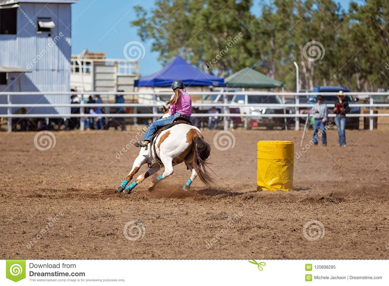 Cowgirl Competing In Barrel Racing Competition At A Rodeo