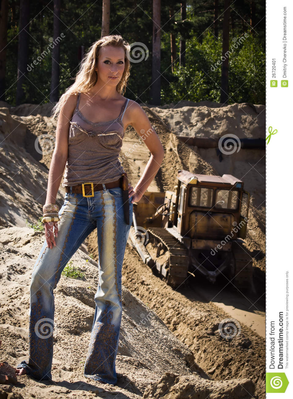 Cowgirl In Jeans Stands Against The Sand Pit Stock Image