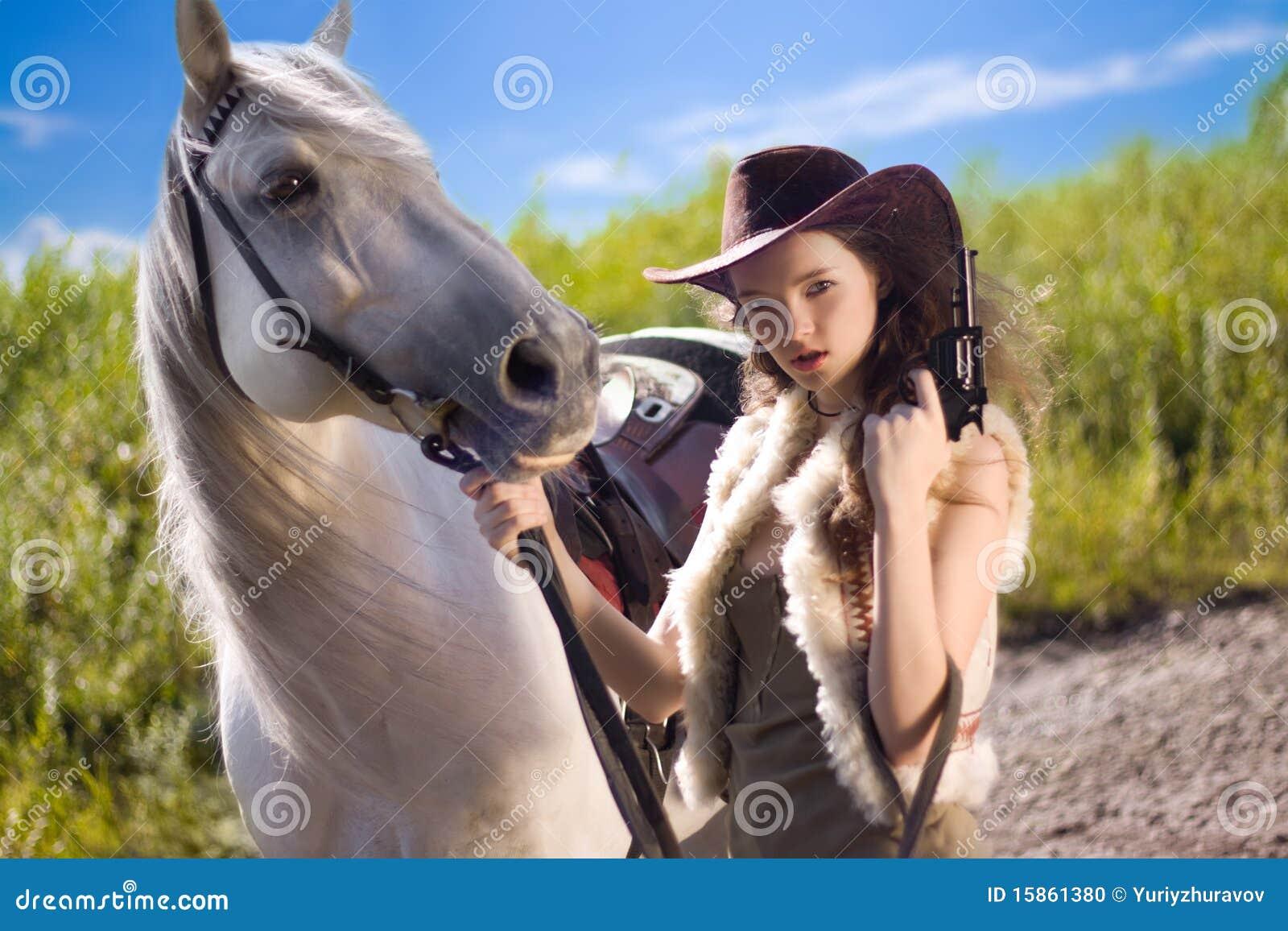 Cowgirl joven con el arma al aire libre