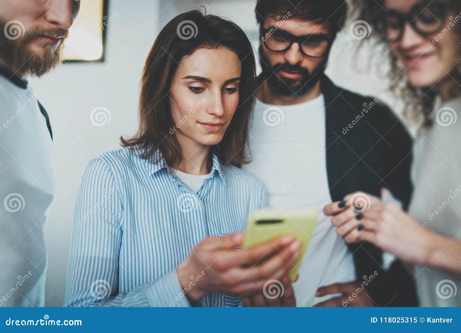 Coworkers biznesowego spotkania pojęcie Młode kobiety trzyma mobilną smartphone rękę i pokazuje informację jej koledzy