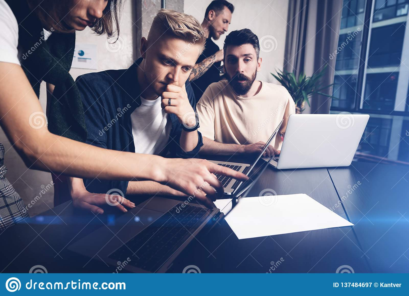 Coworkers team at work. Group of young business people in trendy casual wear working together in creative office