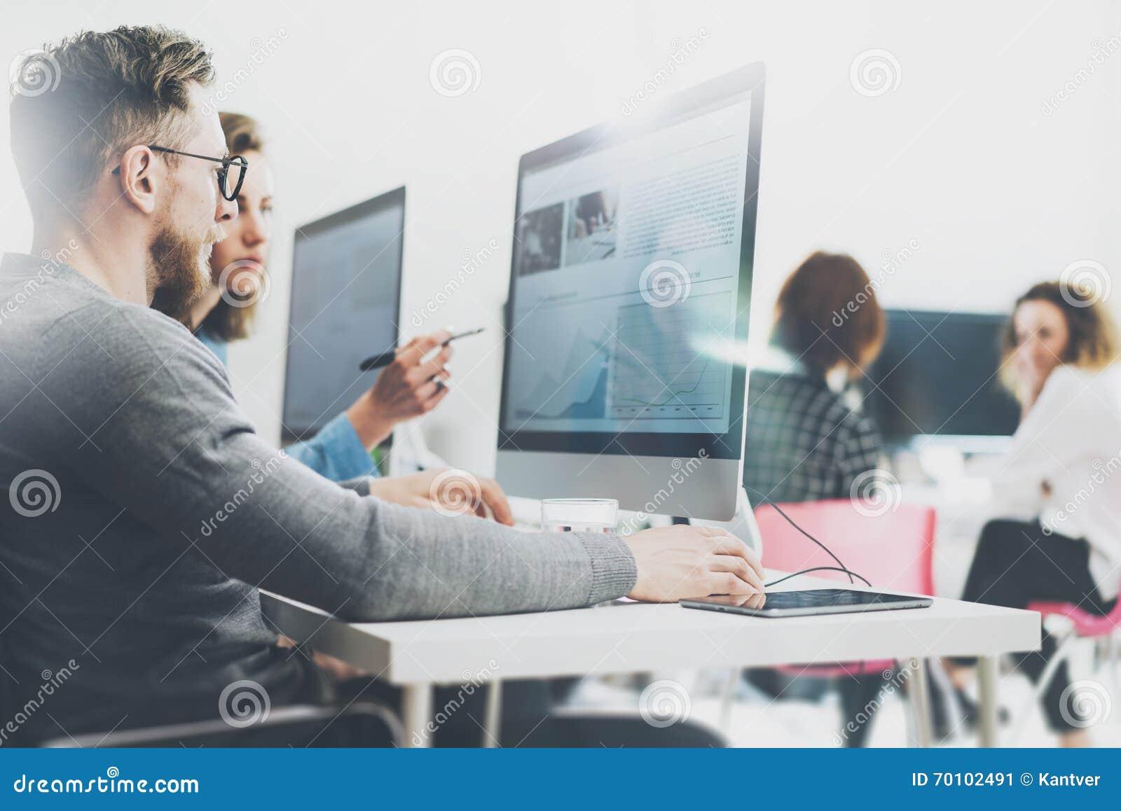 Coworking过程,设计师队工作计划 照片年轻企业乘员组与新的起始的现代办公室一起使用