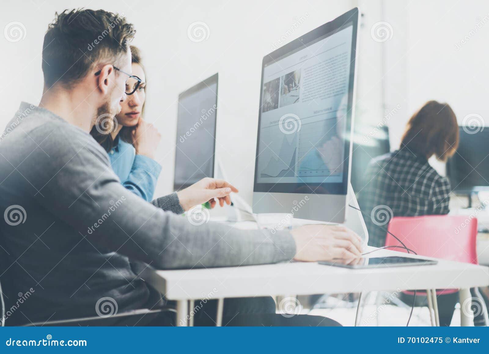 Coworking过程 照片年轻企业乘员组与新的起始的项目现代办公室一起使用 在木头的台式计算机