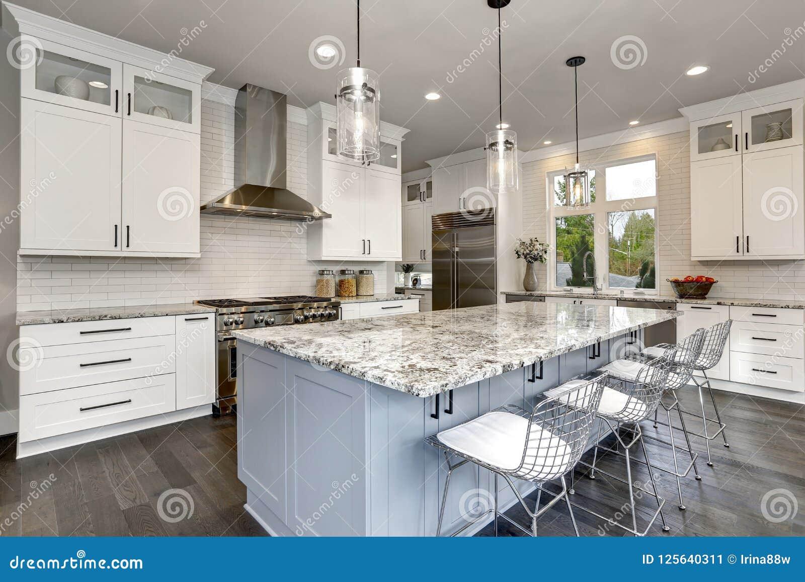 Cozinha bonita no interior moderno home contemporâneo luxuoso com ilha e as cadeiras de aço inoxidável