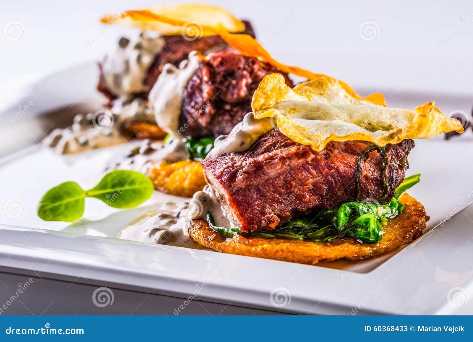 Cozinha culinária Receita: Os mordentes da carne de porco do Confit com espinafres verdes saem do molho de cogumelo do aipo e do