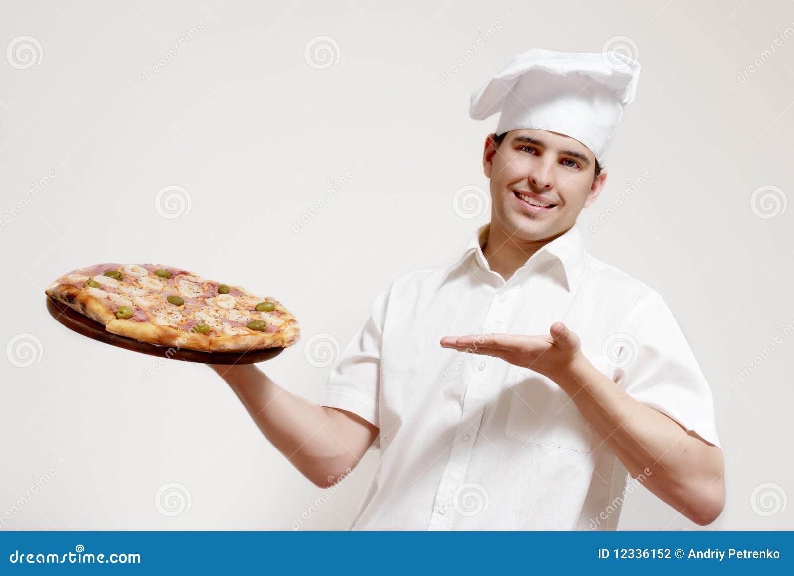 Cozinheiro atrativo feliz com uma pizza nas mãos