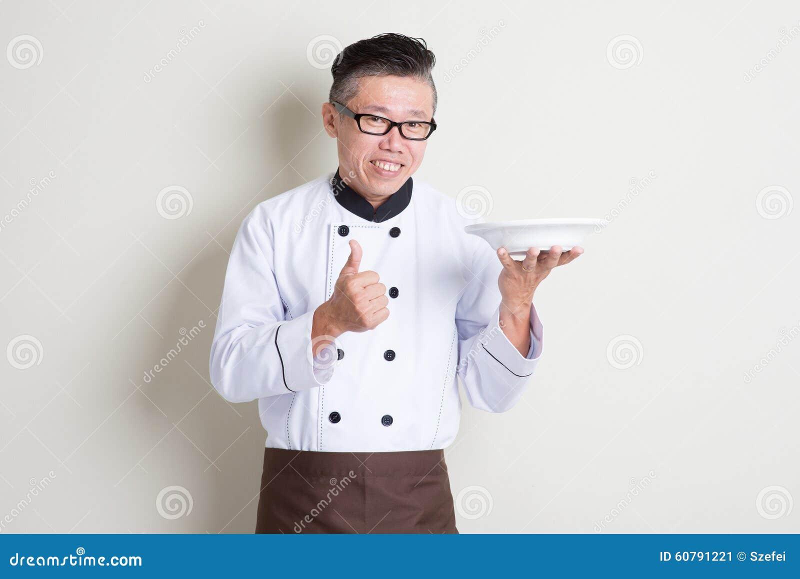 Cozinheiro chefe chinês asiático maduro que apresenta o prato e o polegar acima