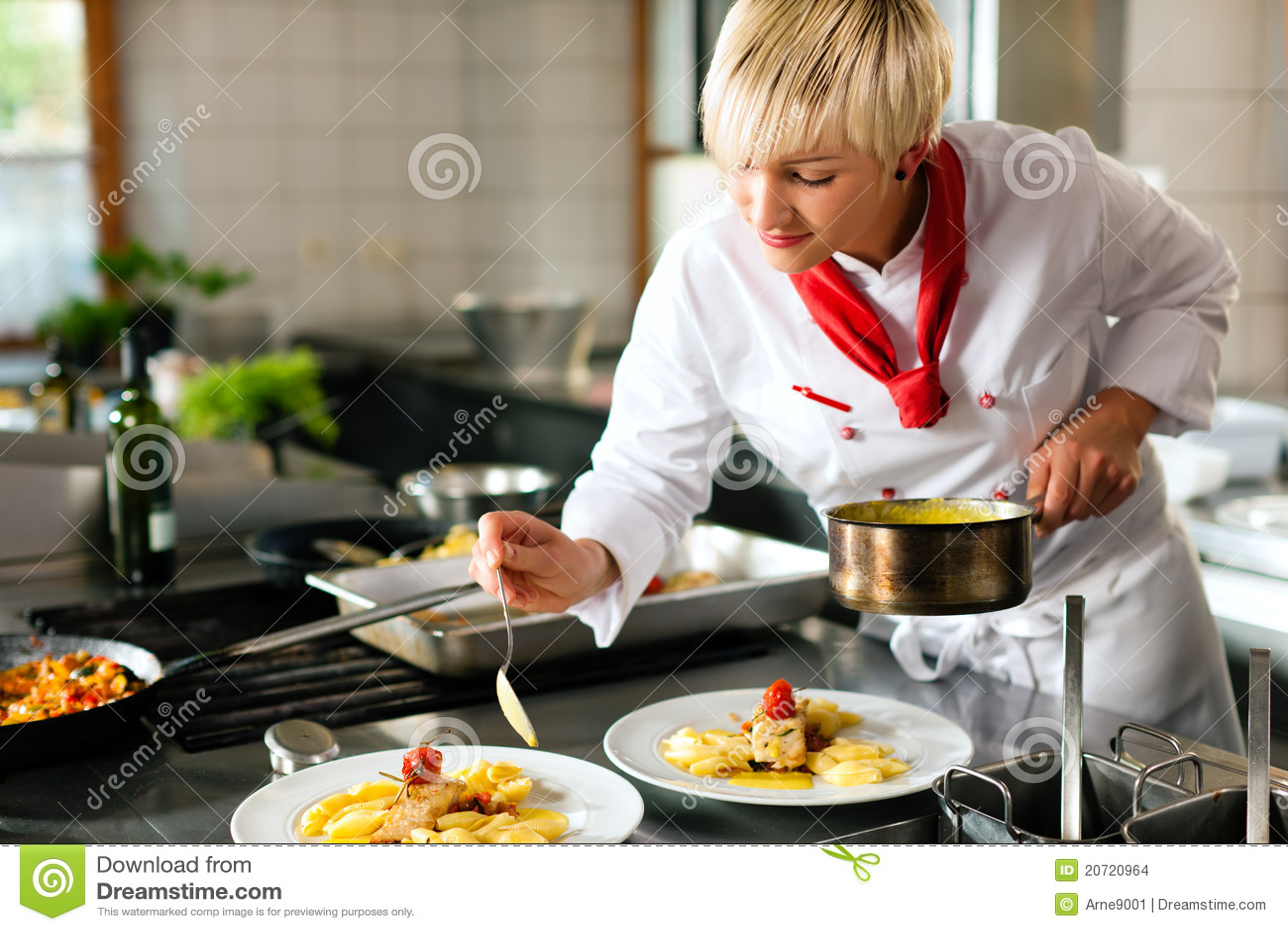 Cozinheiro chefe fêmea em um cooki da cozinha do restaurante ou do hotel