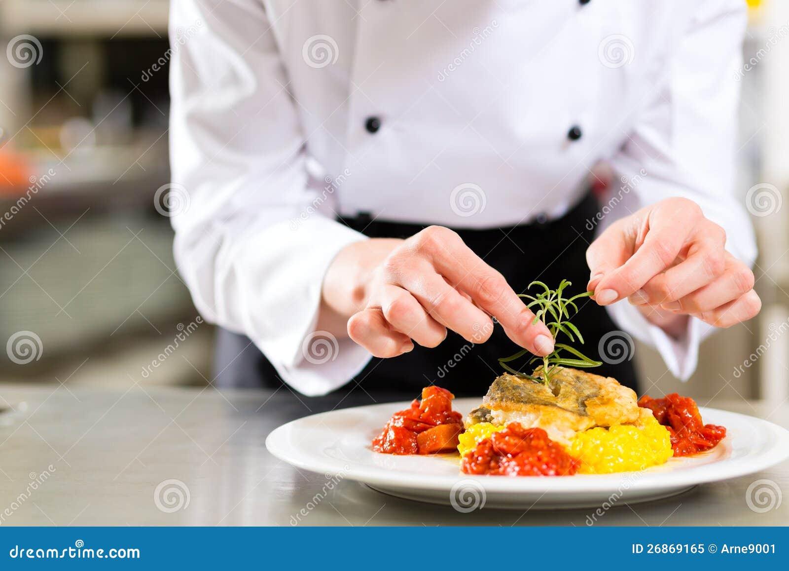 Cozinheiro chefe fêmea no cozimento da cozinha do restaurante