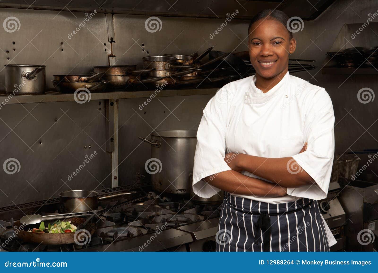 Cozinheiro chefe fêmea que está ao lado do fogão