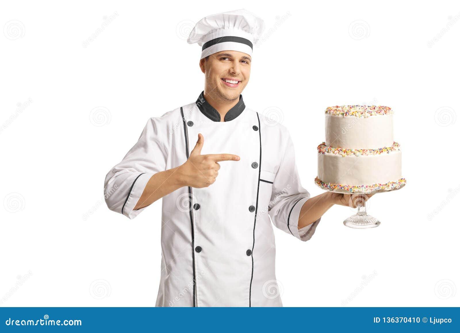 Cozinheiro chefe masculino alegre que guarda um bolo e que aponta nele
