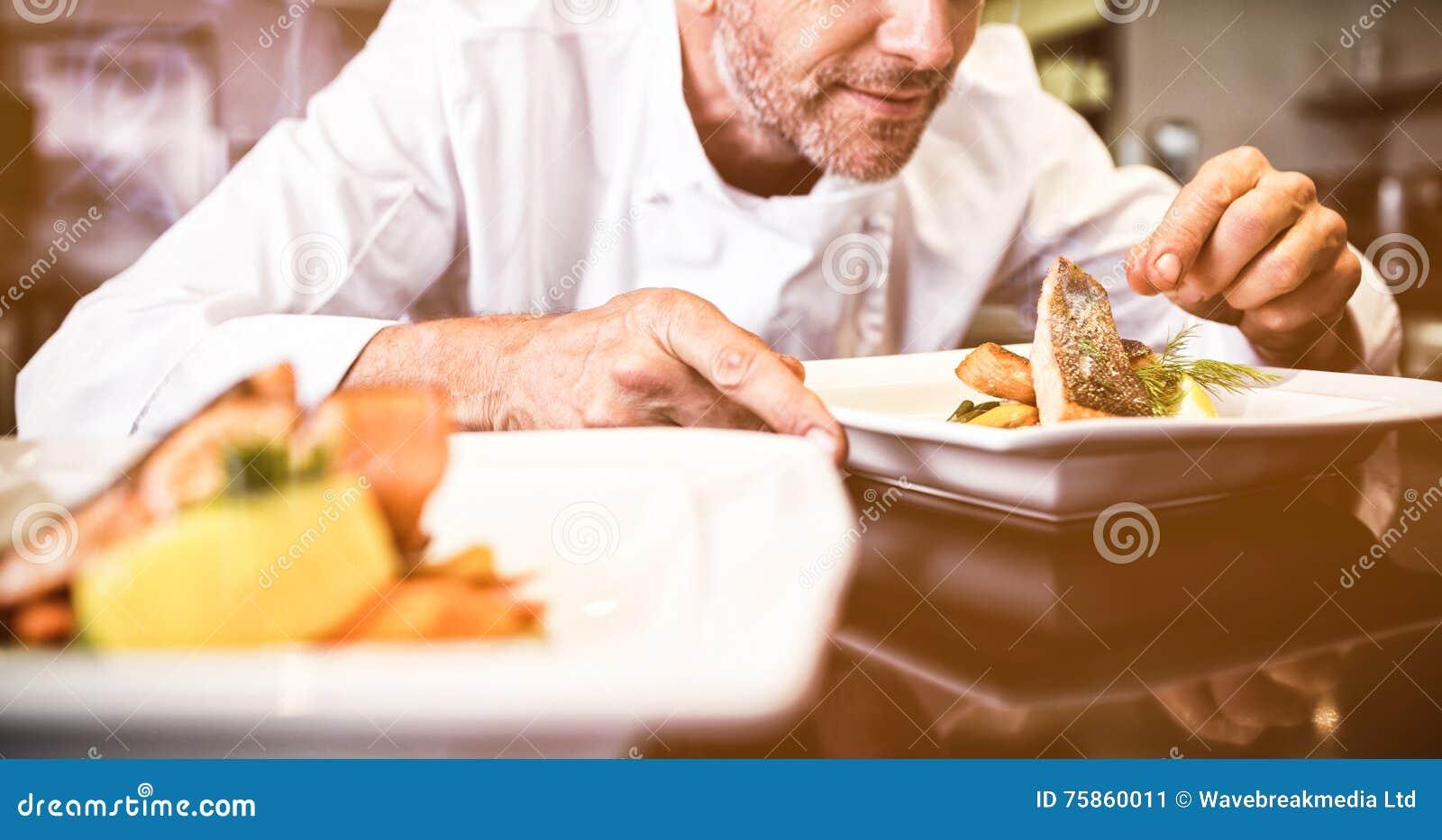 Cozinheiro chefe masculino concentrado que decora o alimento na cozinha