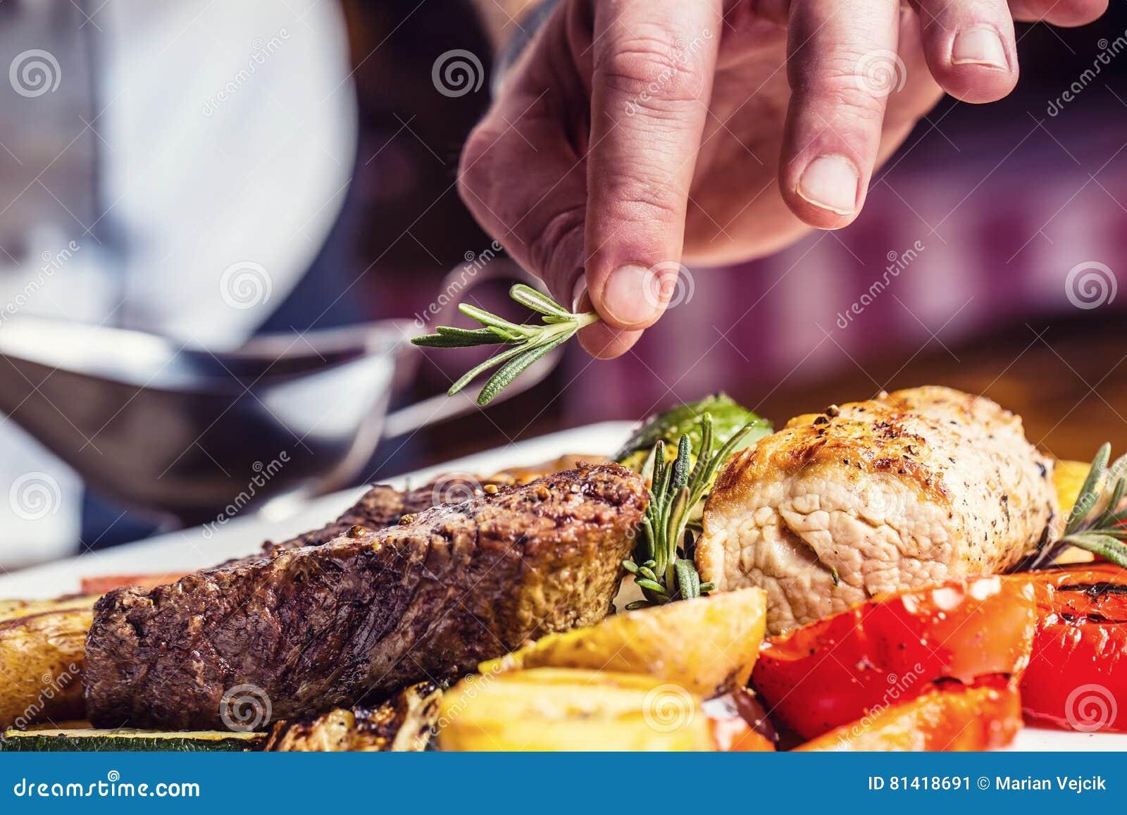 Cozinheiro chefe na cozinha do hotel ou do restaurante que cozinha somente as mãos Bife preparado com decoração vegetal