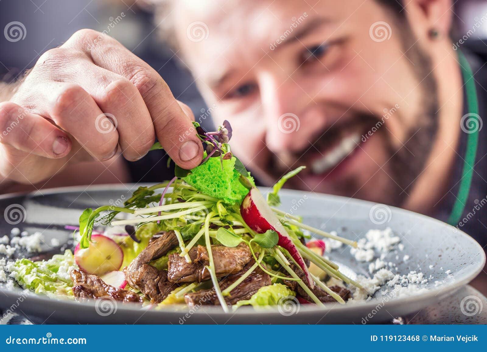 Cozinheiro chefe no hotel ou no restaurante que preparam a salada com partes de carne
