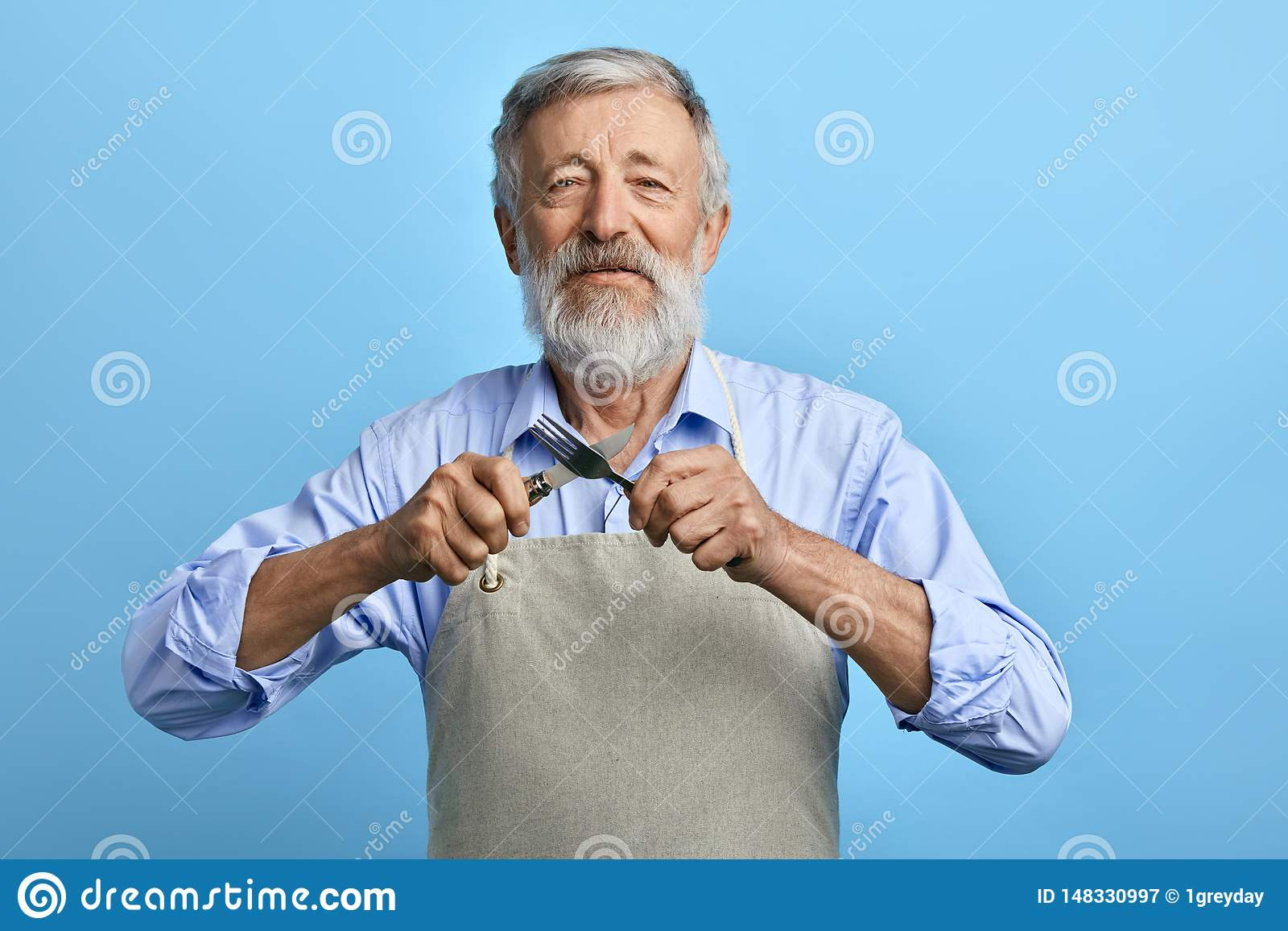 Cozinheiro chefe ou garçom alegre idoso no avental cinzento, forquilha azul da terra arrendada da camisa, colher