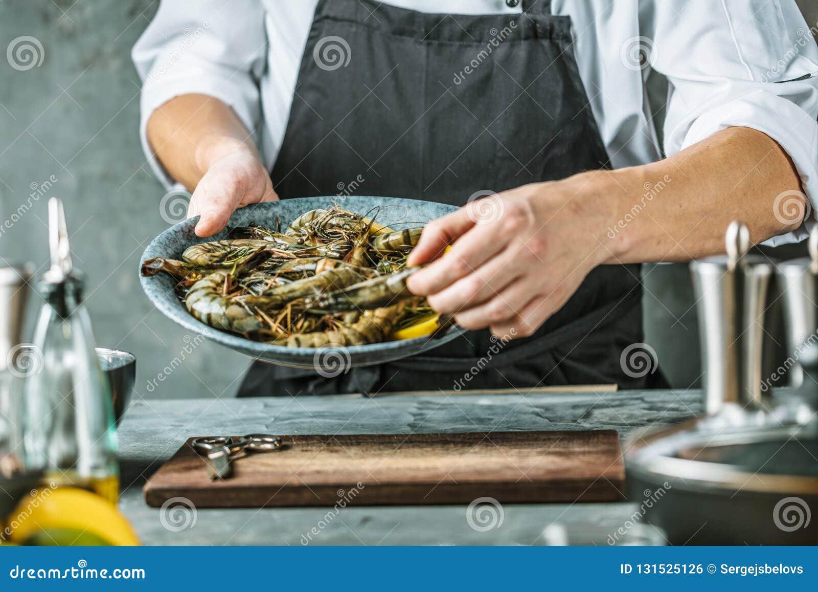 Cozinheiro chefe que cozinha com o camarão do tigre no fundo escuro