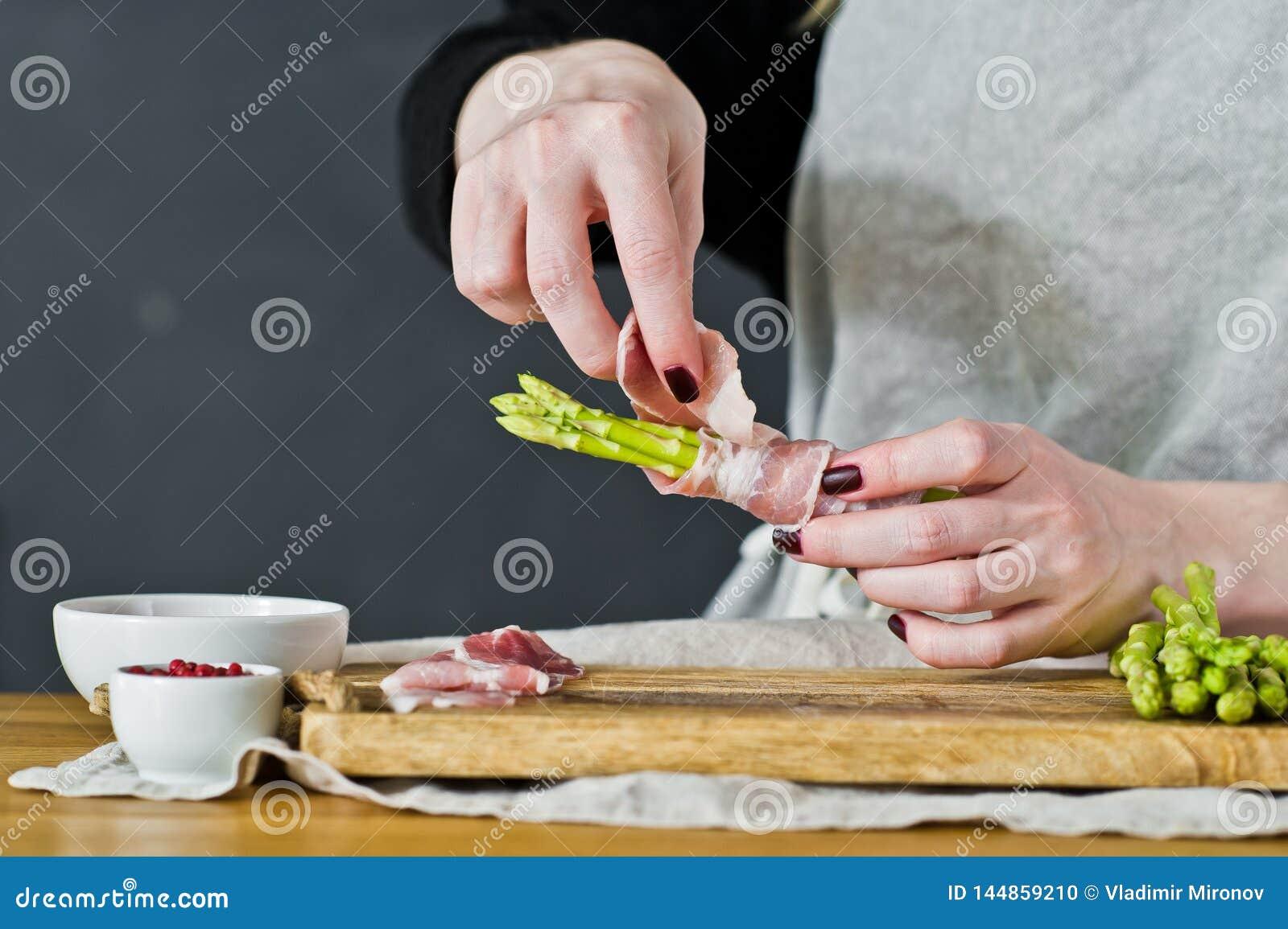 Cozinheiro chefe que cozinha o mini aspargo Vista lateral, fundo da cozinha, conceito de cozinhar o aspargo no bacon