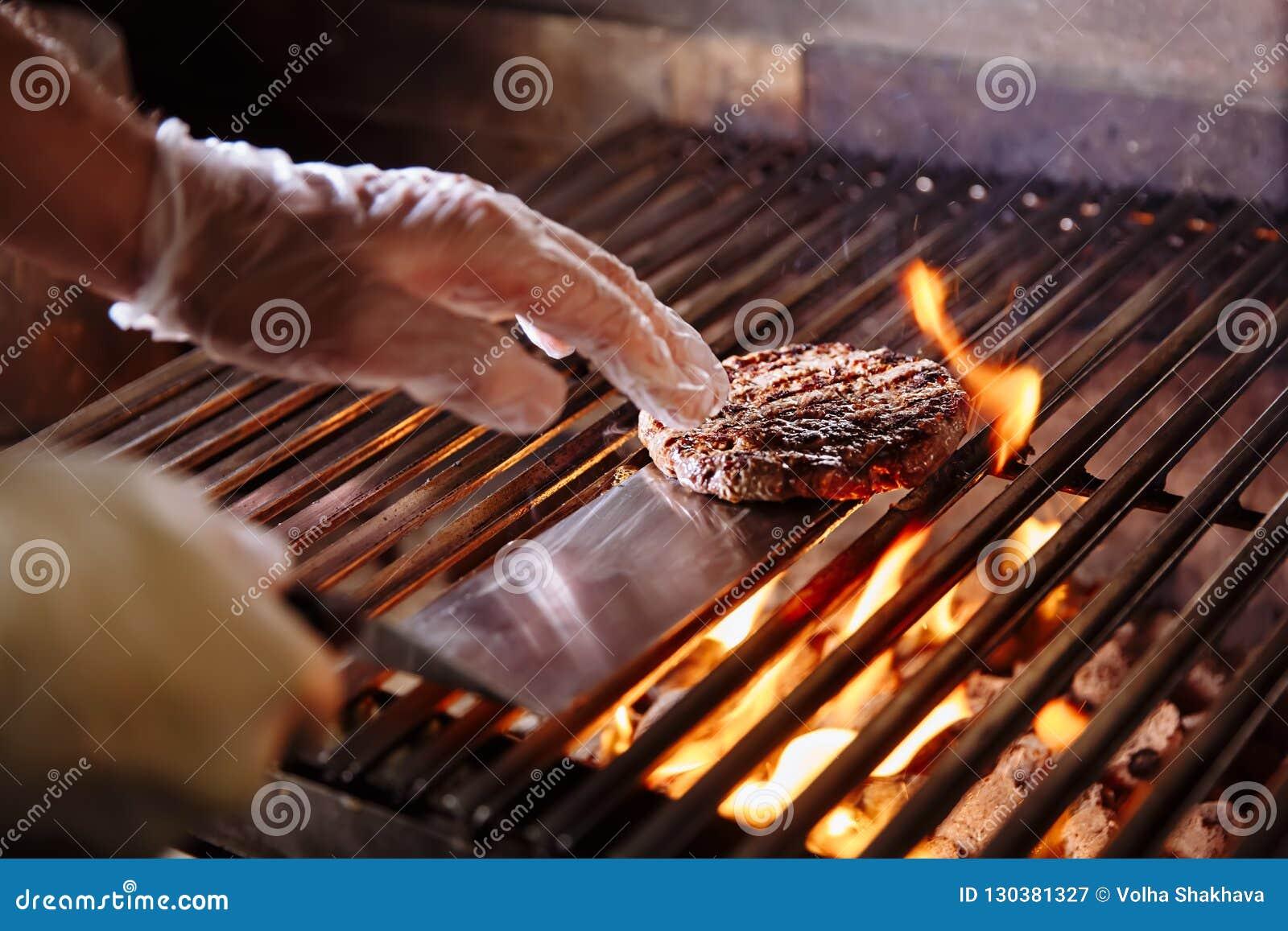 Cozinheiro chefe que faz o hamburguer Os hamburgueres do assado da carne da carne ou de carne de porco para o Hamburger preparado