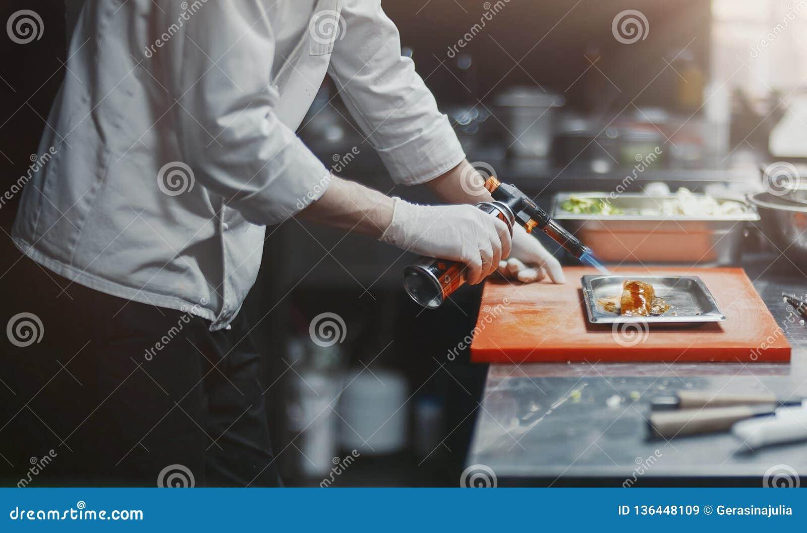 Cozinheiro do cozinheiro chefe do restaurante que prepara o flambe da faixa dos salmões na cozinha aberta