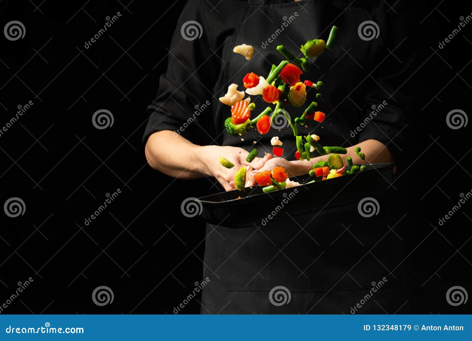 Cozinheiro profissional Prepara um prato com vegetais em uma caçarola no fundo preto, menu, livro da receita, alimento saudável
