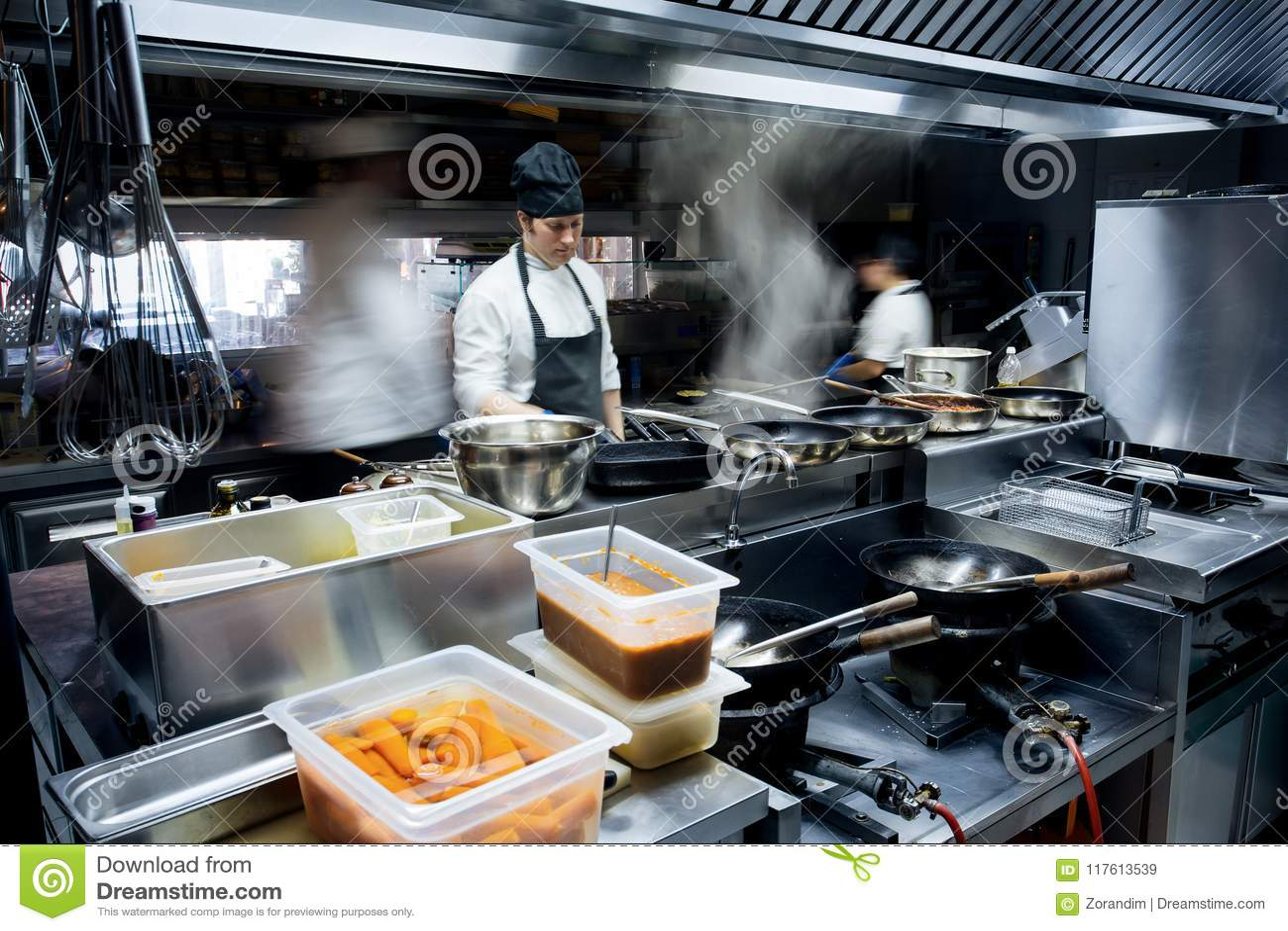Cozinheiros chefe do movimento de uma cozinha do restaurante
