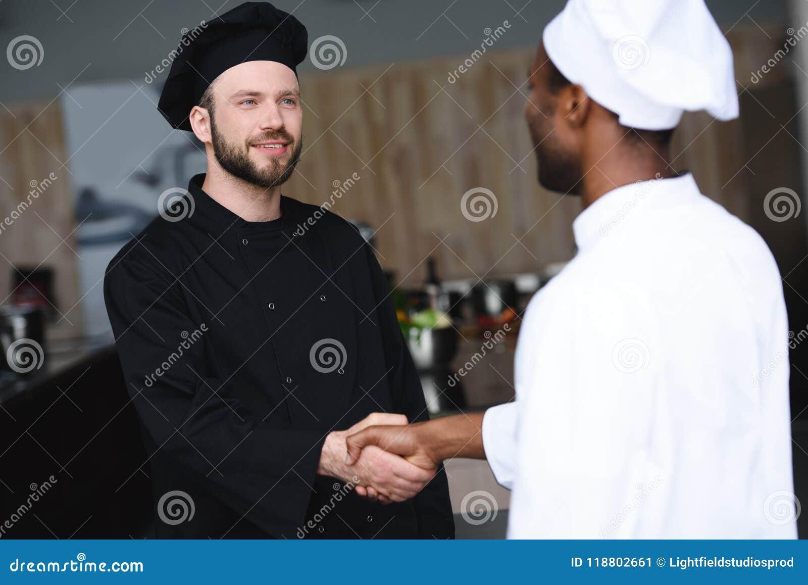 Cozinheiros chefe multiculturais que agitam as mãos
