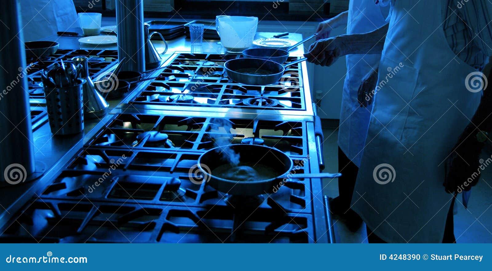 Cozinheiros chefe que trabalham com frigideiras
