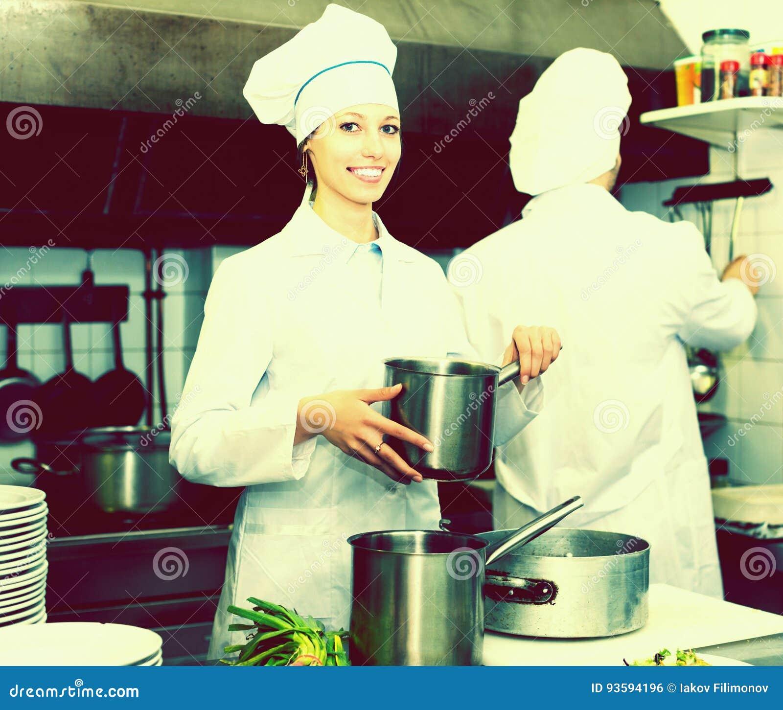 Cozinheiros que cozinham na cozinha profissional