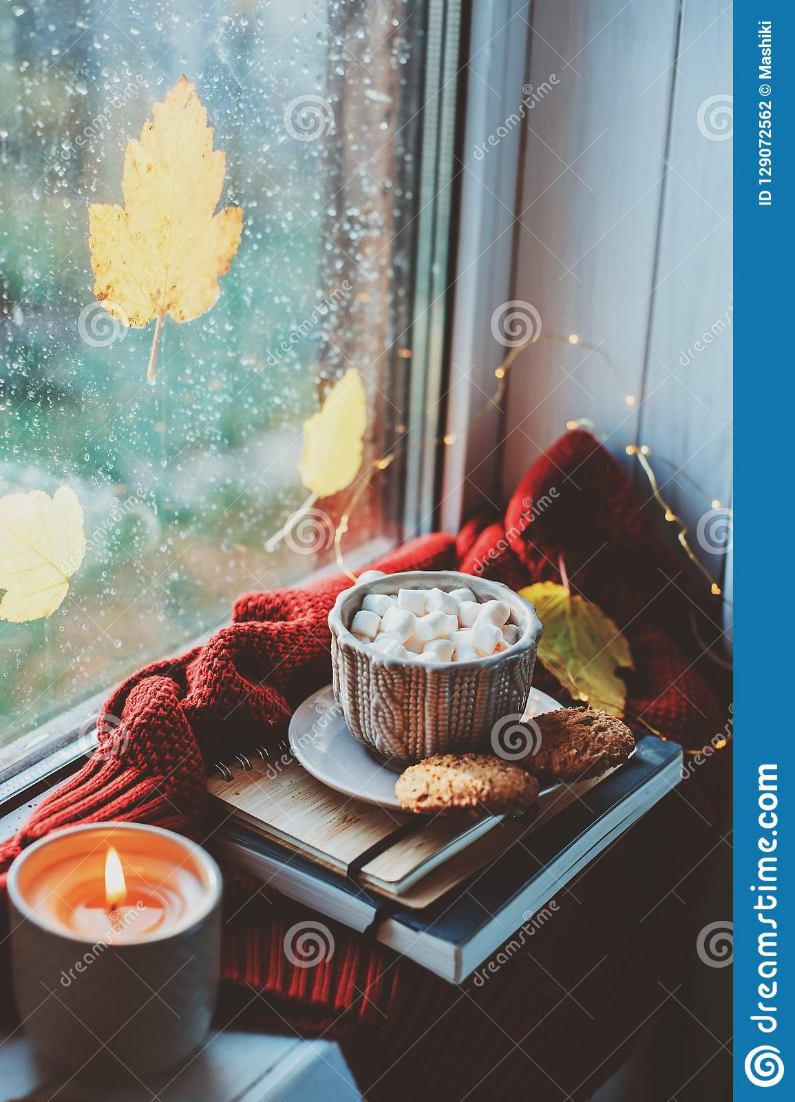 cozy autumn morning at home. Hot cocoa with marshmallows and candle on window in rainy cold day