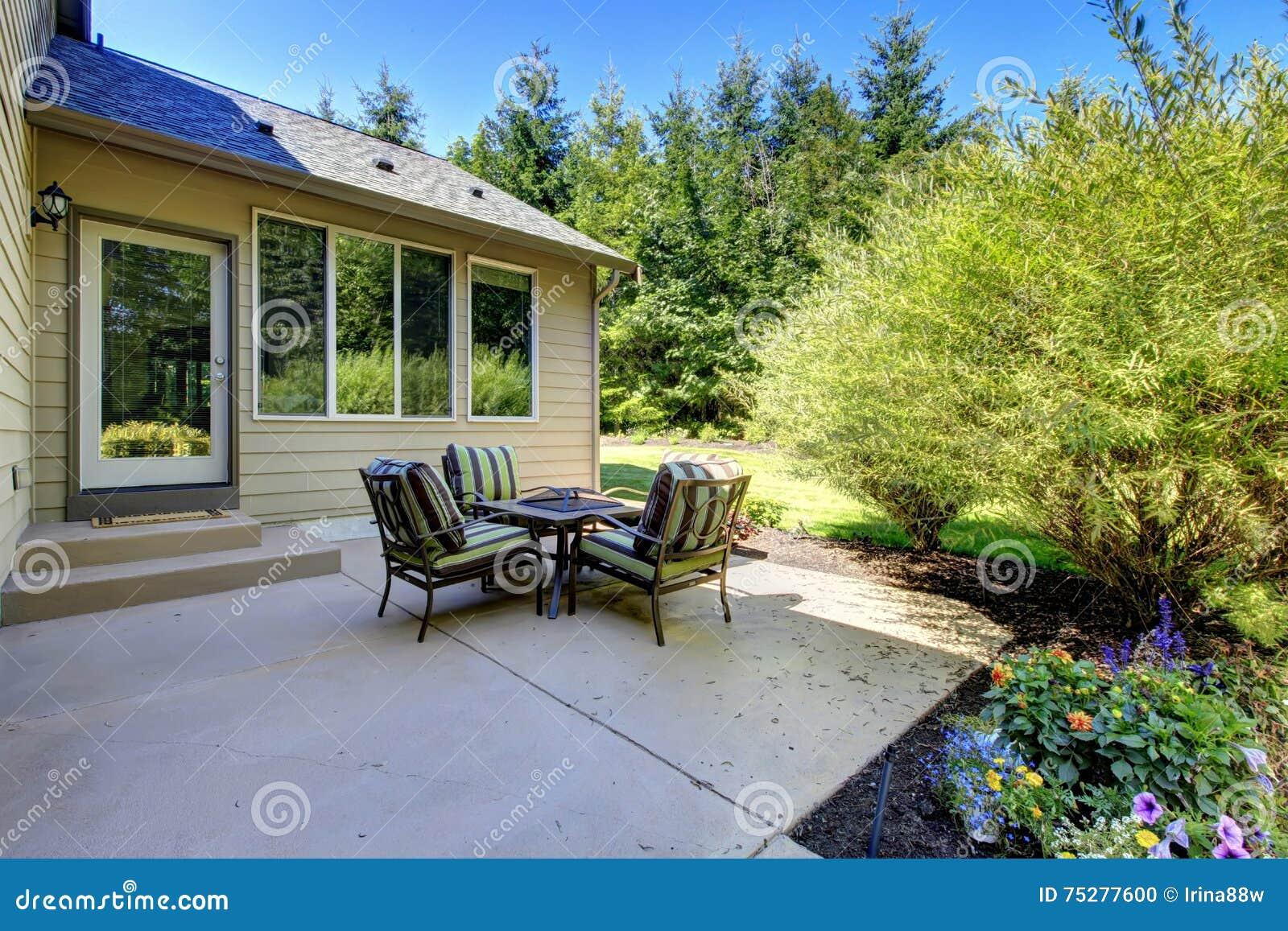 cozy backyard concrete floor patio area with table set stock