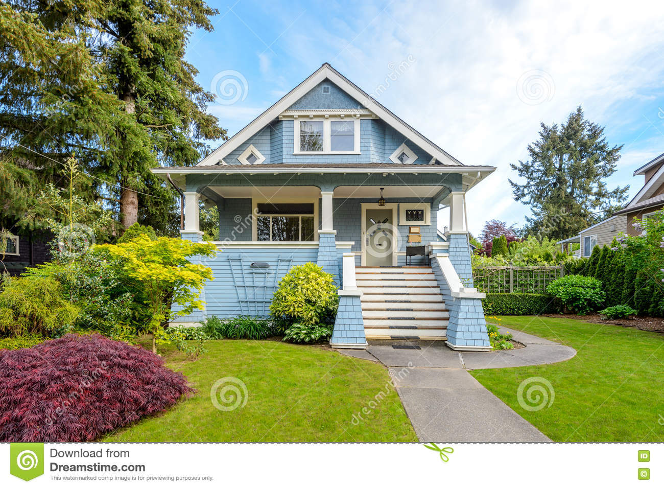 Cozy Blue House With A Beautiful Garden On A Sunny Day Stock Photo