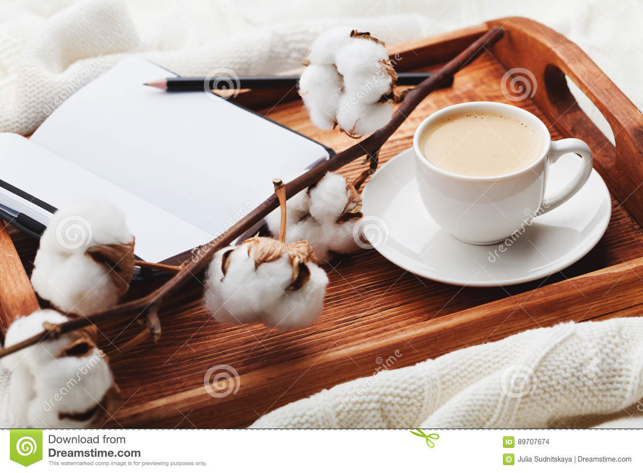 Cozy breakfast with cup of coffee, cotton flower and open notebook on rustic wooden tray in bed.