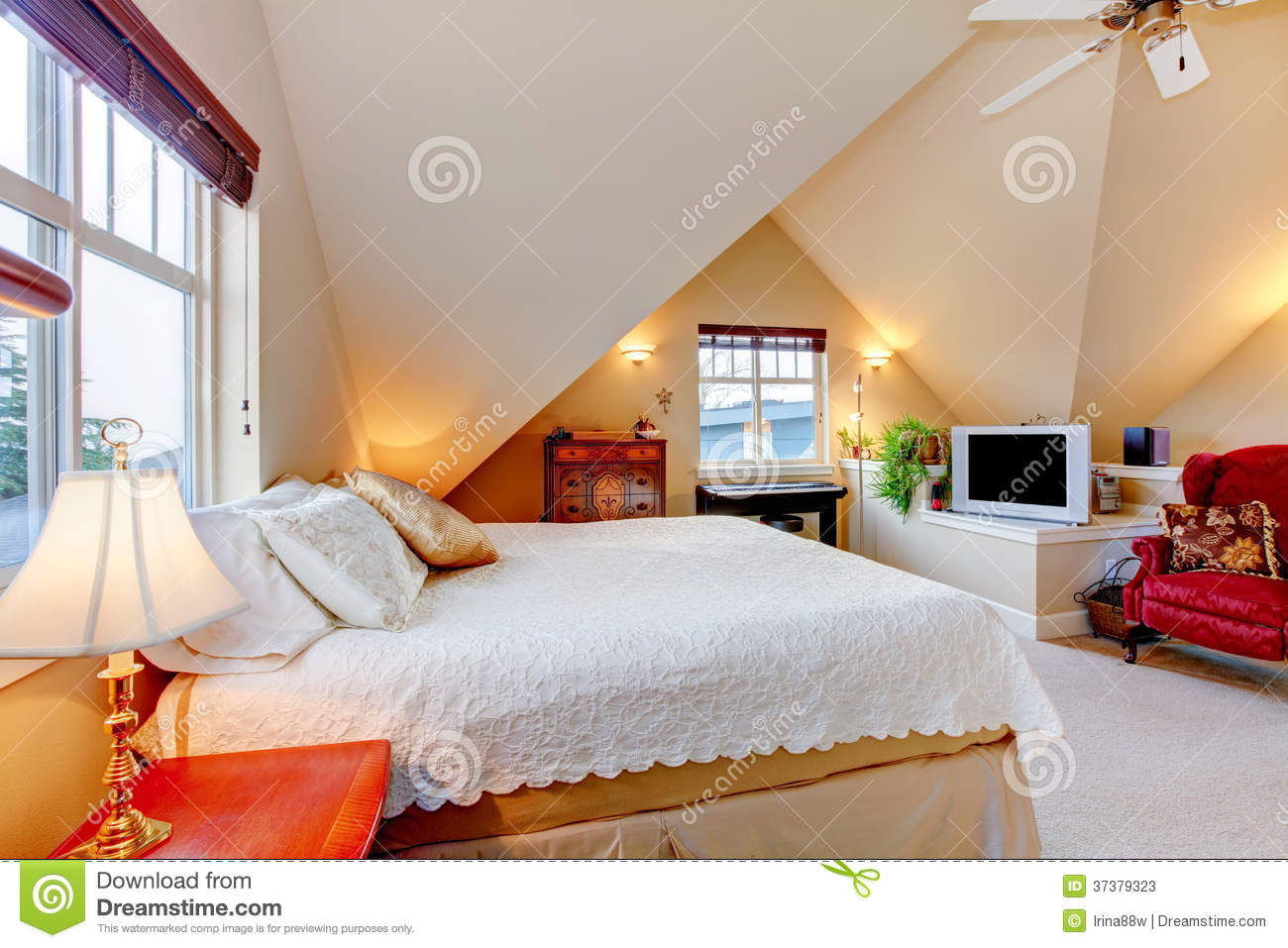 cozy bright bedroom with cream color vaulted ceiling stock