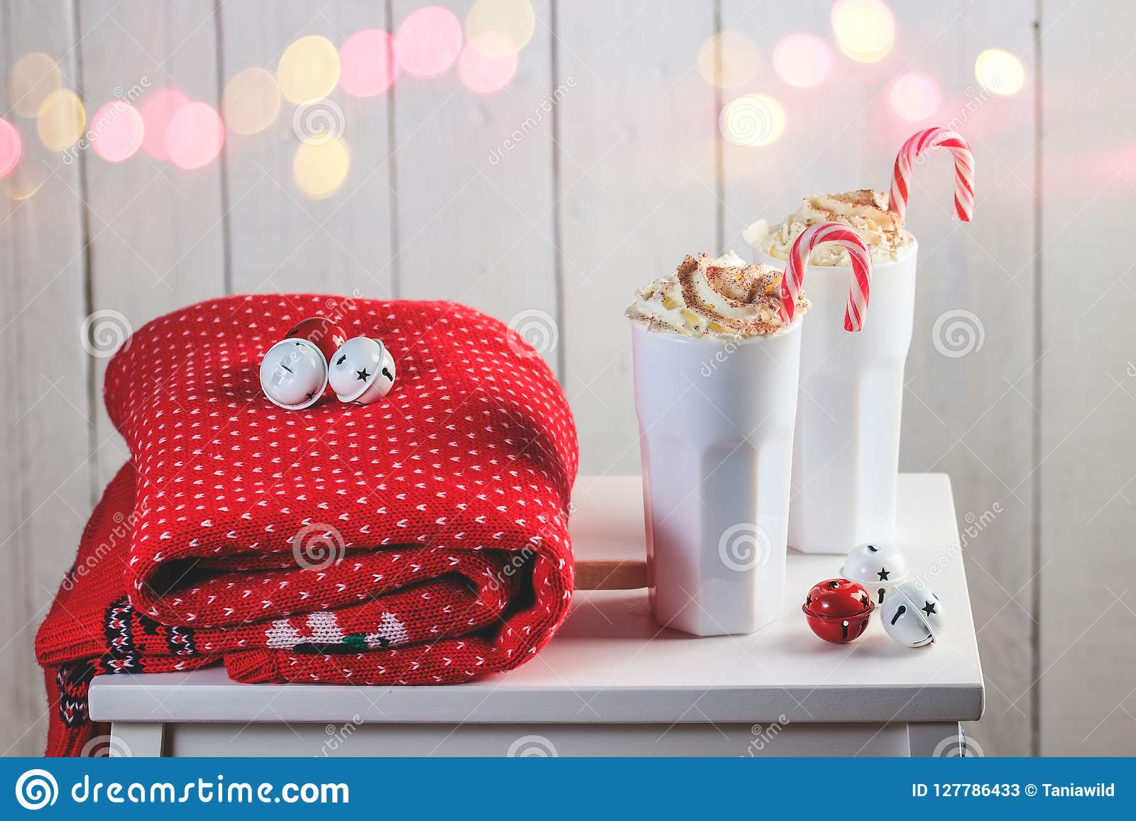 Cozy Christmas composition.Two mug with hot drinks, chocolate with whipped cream and Candy Canes in front of a light wooden backgr