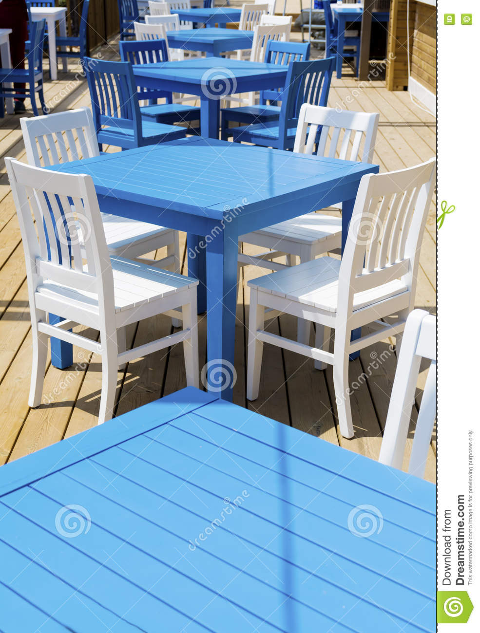 Cozy Greek Restaurant With White Chairs And Blue Tables Stock Image - Restaurant table cost