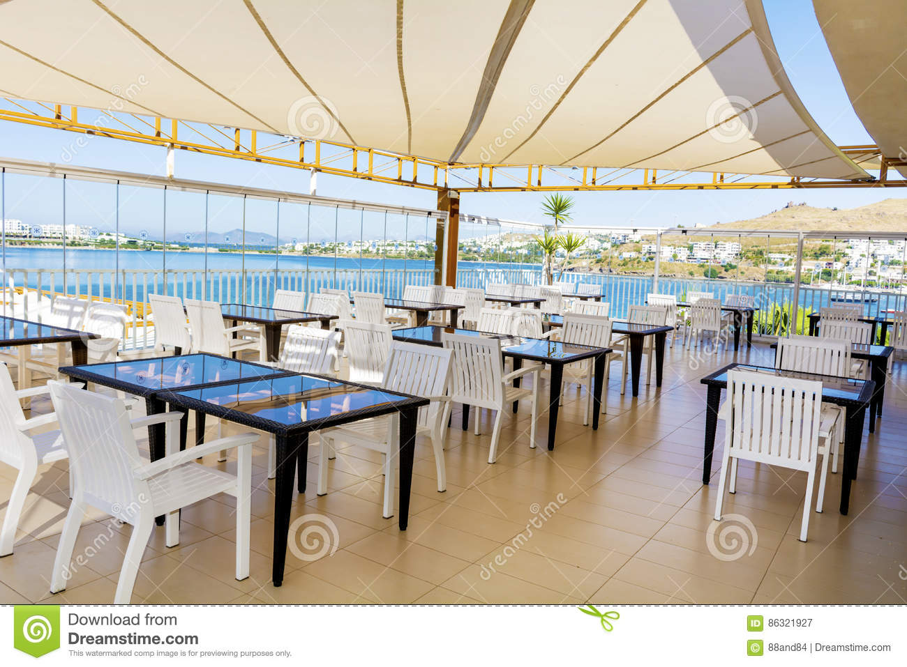 Cozy greek restaurant with white chairs and blue tables