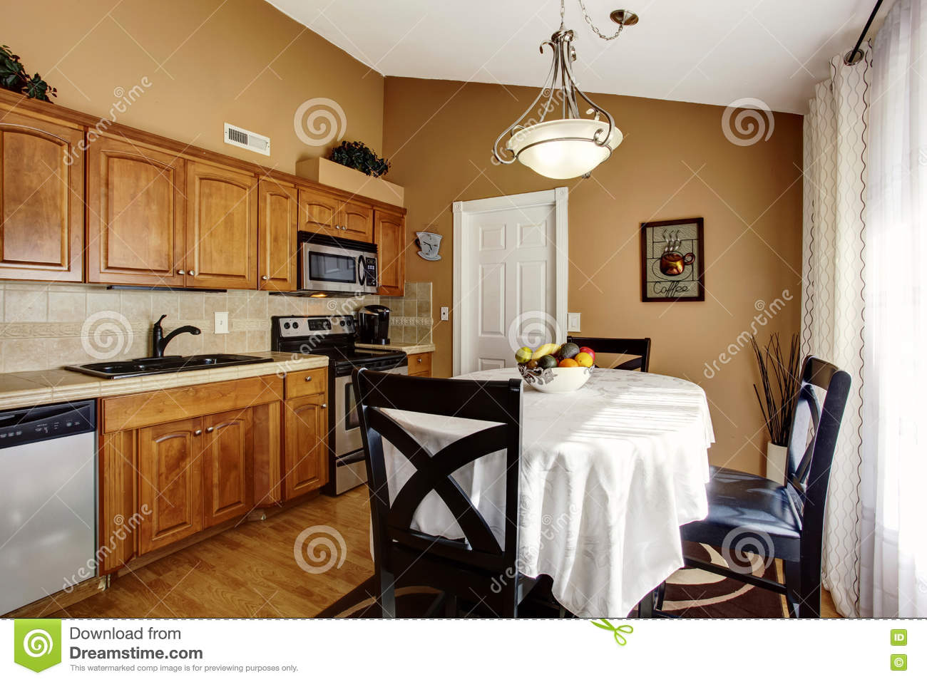 Cozy Kitchen And Dining Room Interior With Black Table Set Brown Cabinets