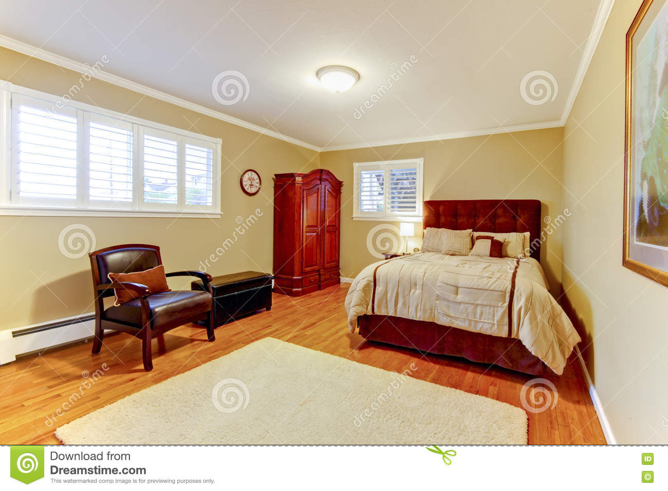 Cozy large guest room with suede brown bed and armor hardwood floors and beige walls